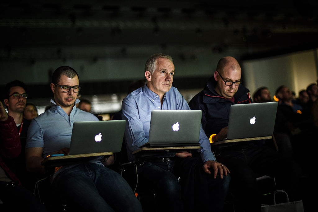 Journalists work on their Apple laptops