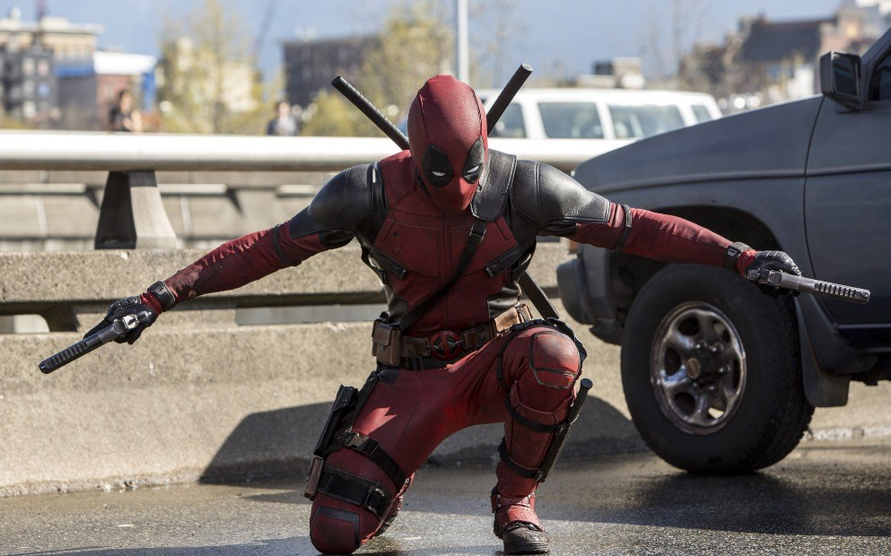 Deadpool holding two guns and kneeling next to a car.