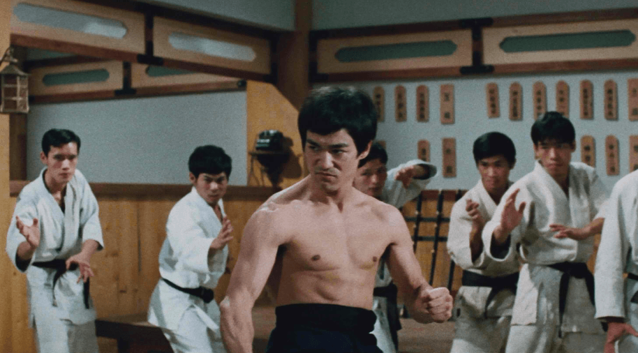 A shirtless Bruce Lee, surrounded by a group of kung fu students in a dojo