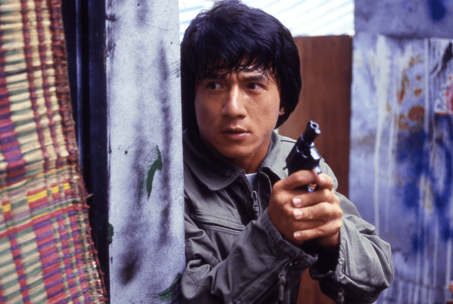 Jackie Chan hiding behind a corner, holding a pistol with both hands