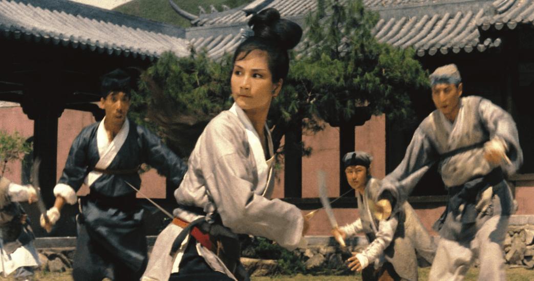 A women brandishing a sword, surrounding by assailants in a courtyard