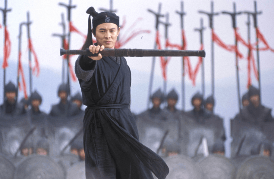 Jet Li holding a sheathed sword out in front of him, standing in front of troops in a line