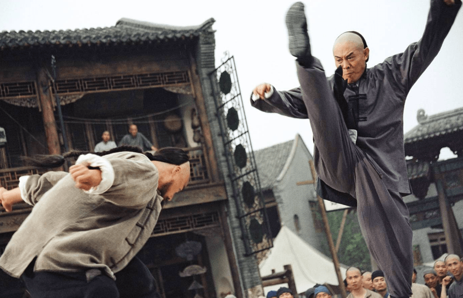 Jet Li kicks his right leg all the way up, jumping at an assailant bending over with both his arms out