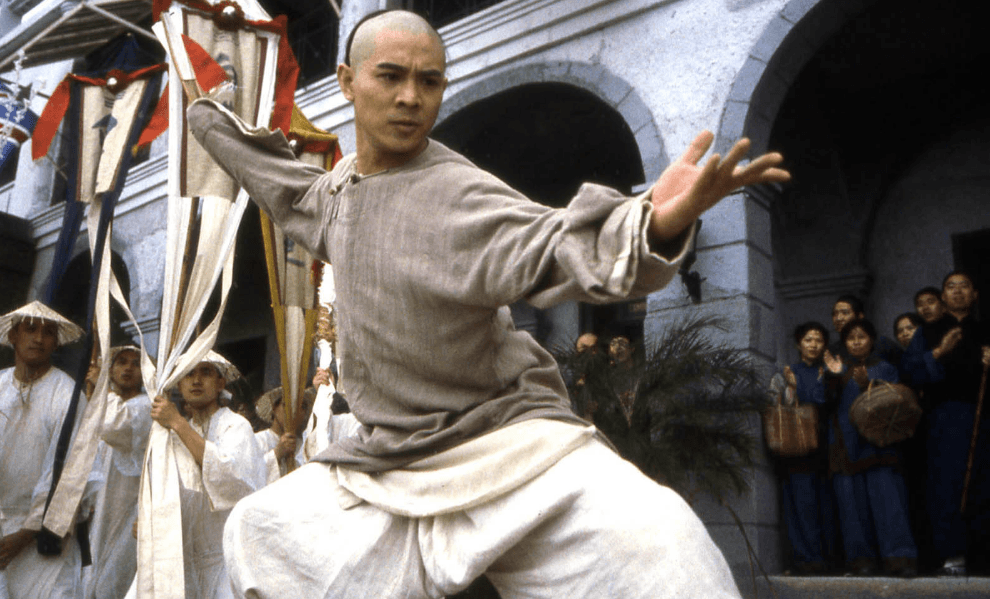 Jet Lee with his left hand open and out, as he crouches, ready to fight