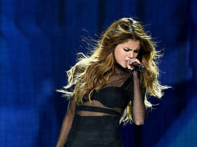 Selena Gomez performs at Staples Center, holding a microphone in her hand.