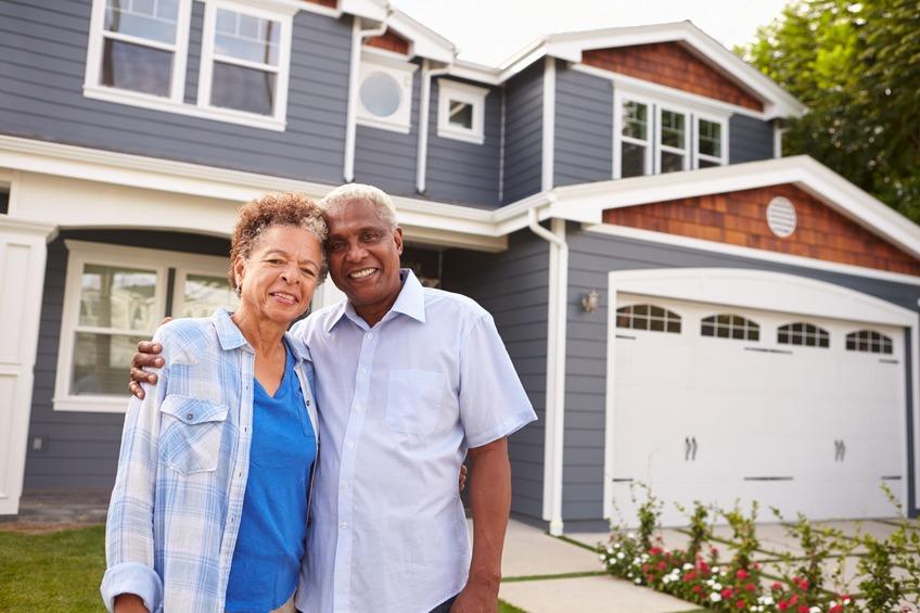 Senior black couple standing outside their house