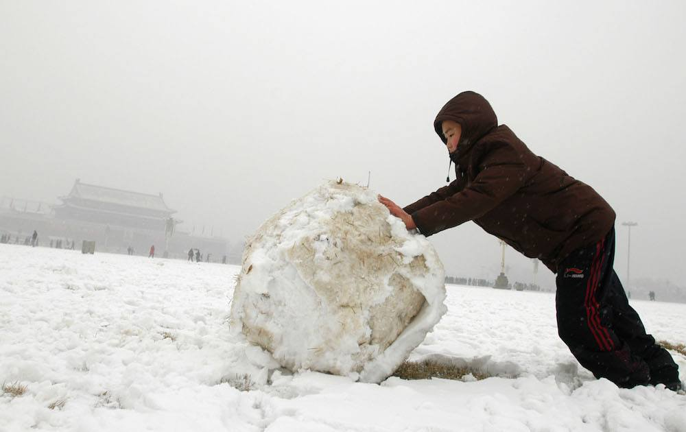 boy rolling a snowball