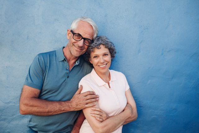 Happy middle aged man and woman against a wall.