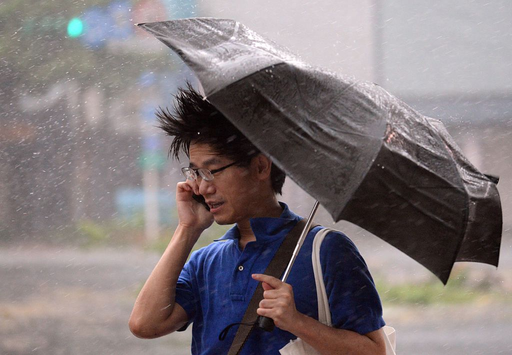 A man speaks on the phone as typhoon Soudelor hits Taipei