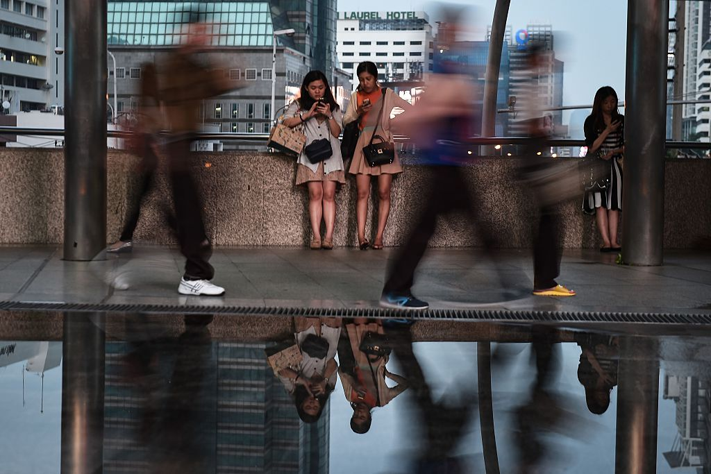 people on their mobile phones in the central business district of Bangkok