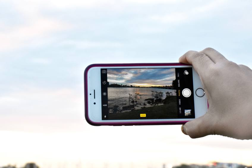 A person taking a picture of the sunset with an iPhone