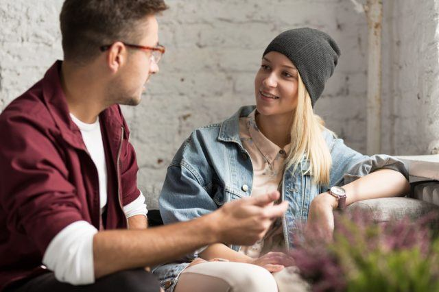 hipster couple talking in cozy cafe