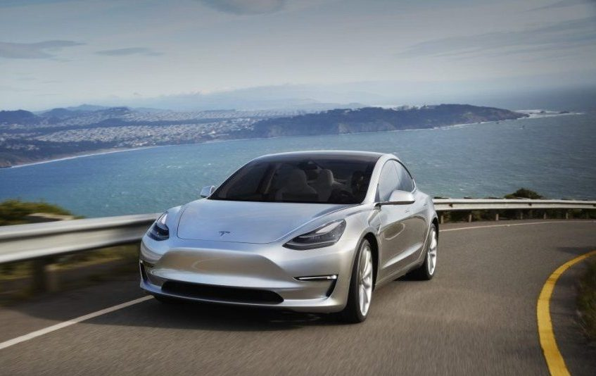 Road shot of silver Tesla Model 3 on California coast