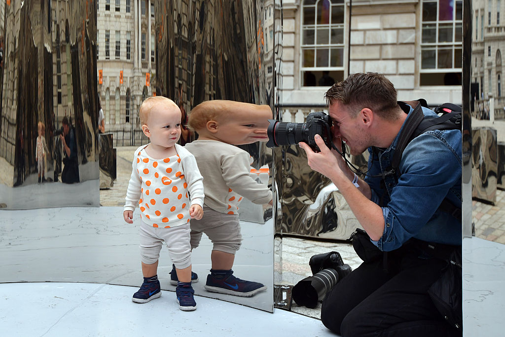 17-month-old Hugo Baumann Malcolmson is reflected as he is photographed