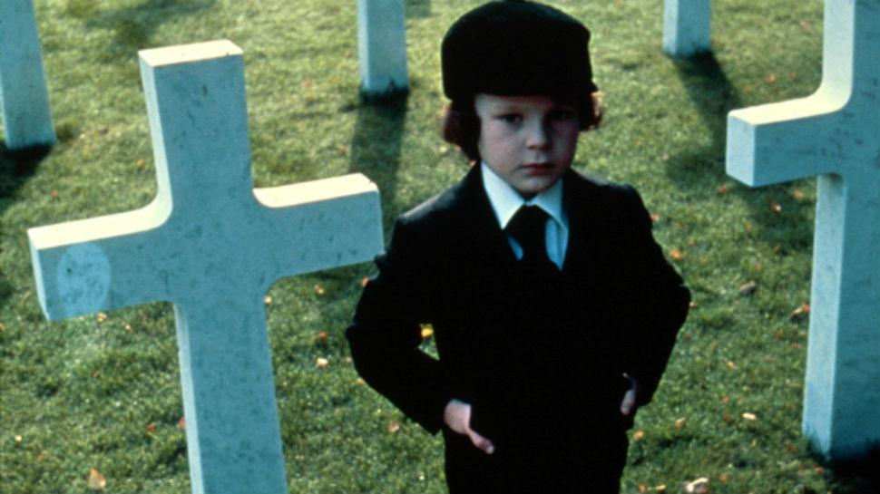 A young boy stands in a graveyard in a black suit and hat in The Omen
