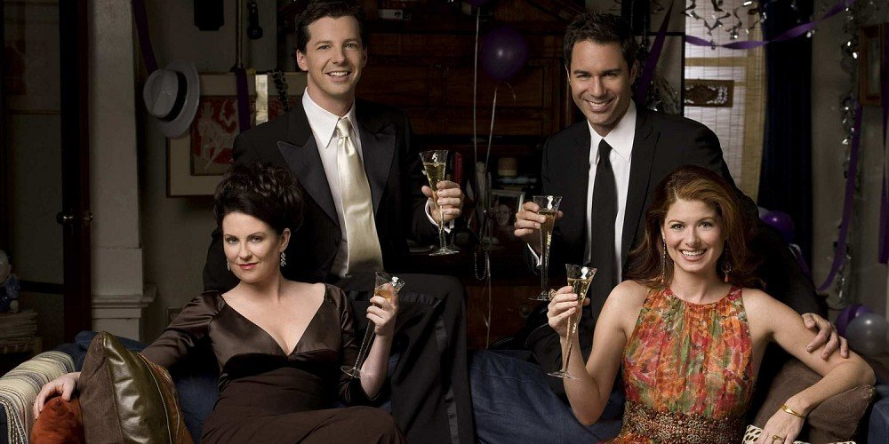 Will and Grace cast pose while holding champagne flutes