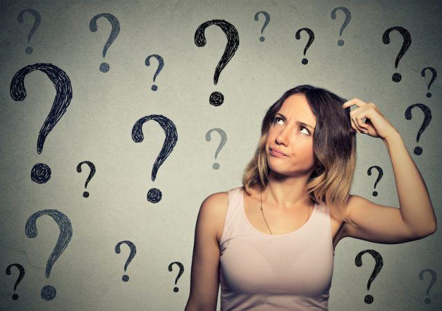 Thinking young woman looking up at many question marks