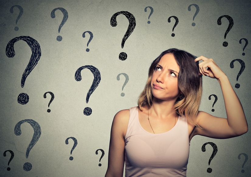 A young woman scratches her head while looking up at question marks painted on a wall