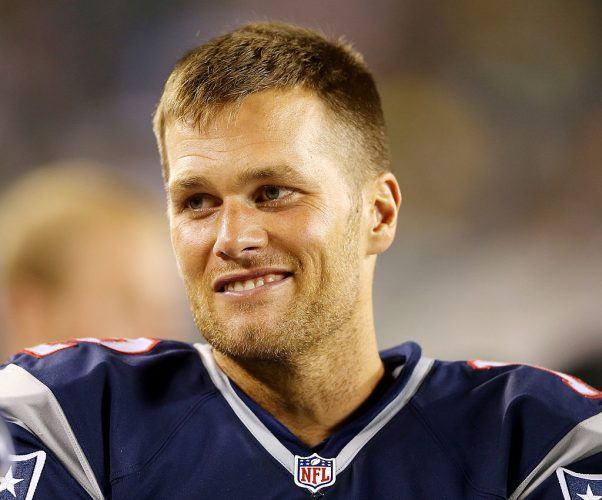 Tom Brady smiles while wearing his NFL jersey.