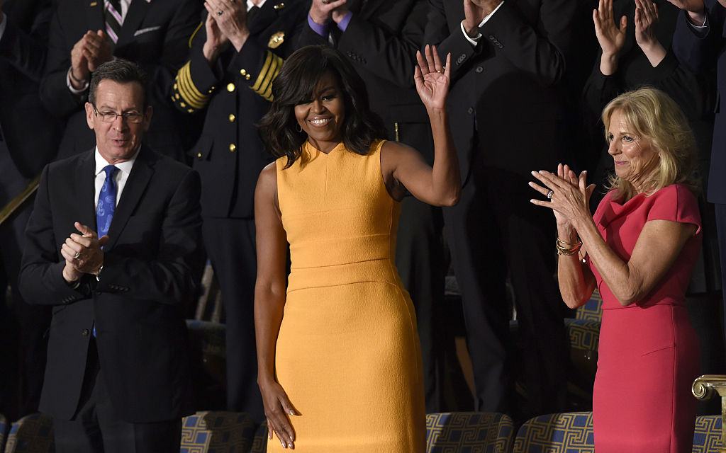 US First Lady Michelle Obama (C) waves, with Jill Biden (R) wife of US Vice President Joe Biden