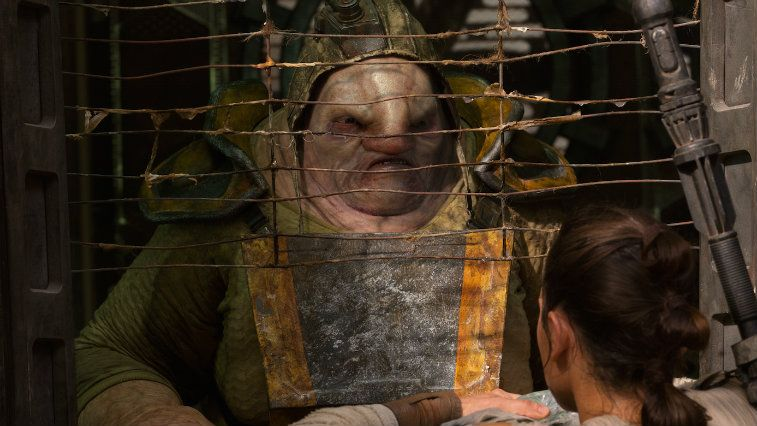 Unkar Plutt stands behind barbed wire in Star Wars: The Force Awakens