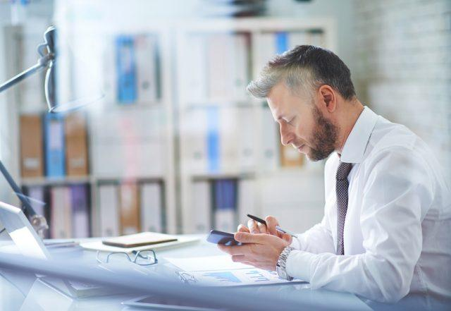 Businessman texting in his office