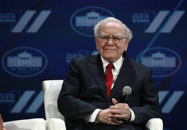 Warren Buffett holding a microphone while sitting in a white chair.