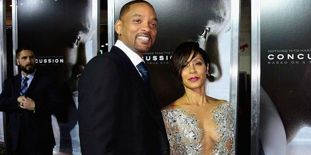 Will and Jada Pinkett-Smith smile while posing on a red carpet.