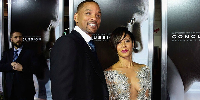 Will and Jada Pinkett-Smith smile for cameras on the red carpet of Concussion