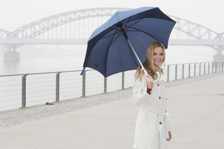 Woman in white coat carrying blue umbrella