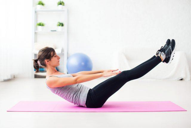Woman doing abdominal exercise on a pink mat.