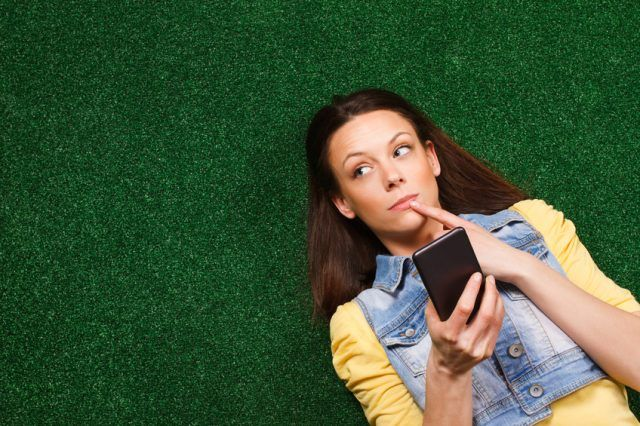 young woman is lying on the grass and thinking