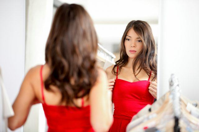 Woman trying clothing looking in mirror adjusting dress