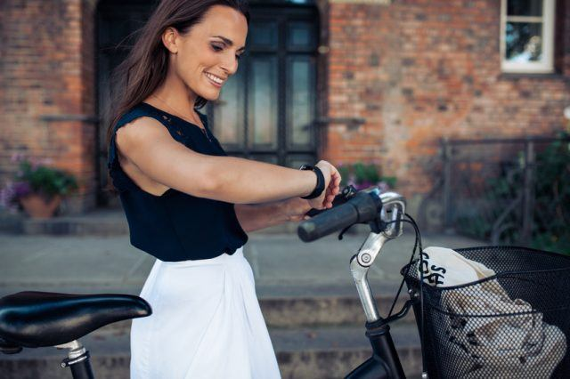 woman with a bike checking the time on her wristwatch