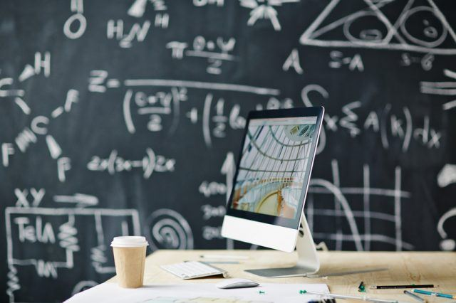 Computer on a table with blackboard in the background