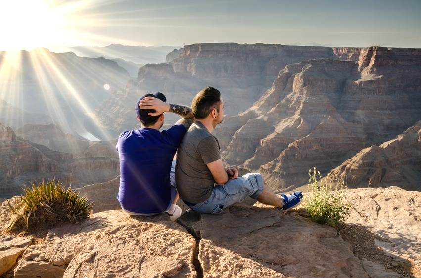 A young male couple looking into the Grand Canyon