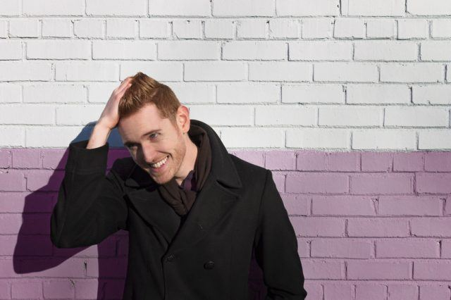 male redhead posing in front of a colored brick wall