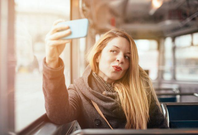 A woman takes a selfie while riding public transportation