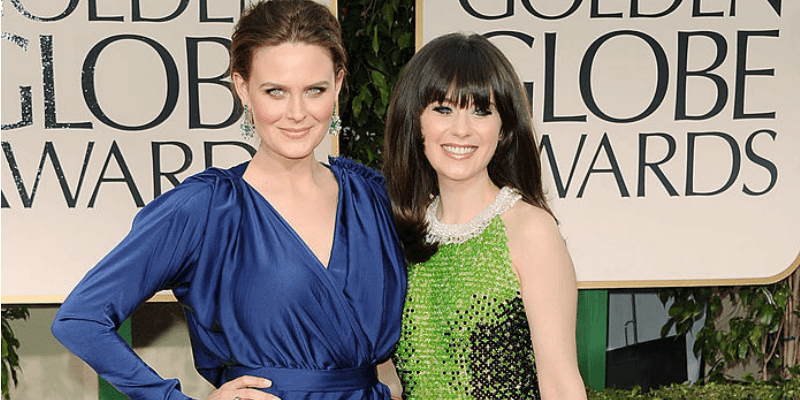 Zooey Deschanel and Emily Deschanel pose together on the red carpet.
