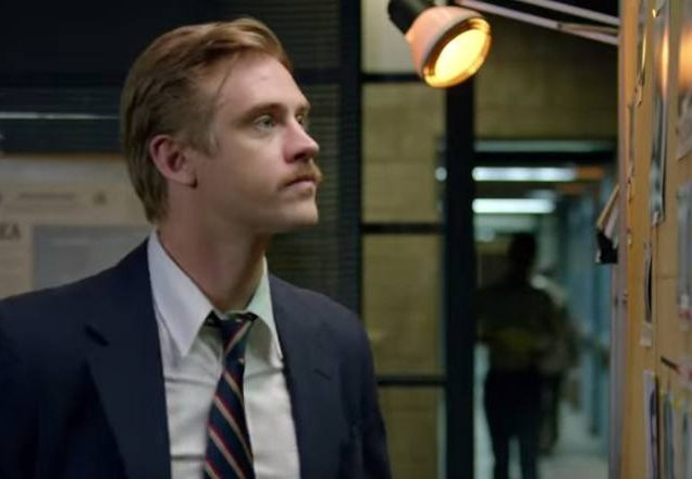 Boyd Holbrook wears a suit and looks at a bulletin board in Narcos Season 2