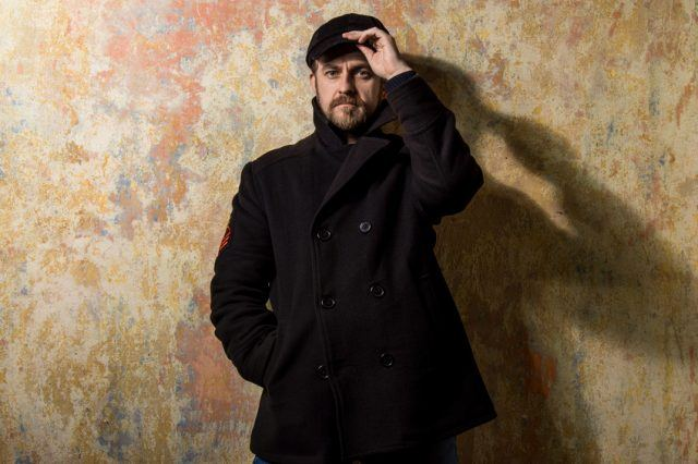 young bearded man in a pea coat and cap