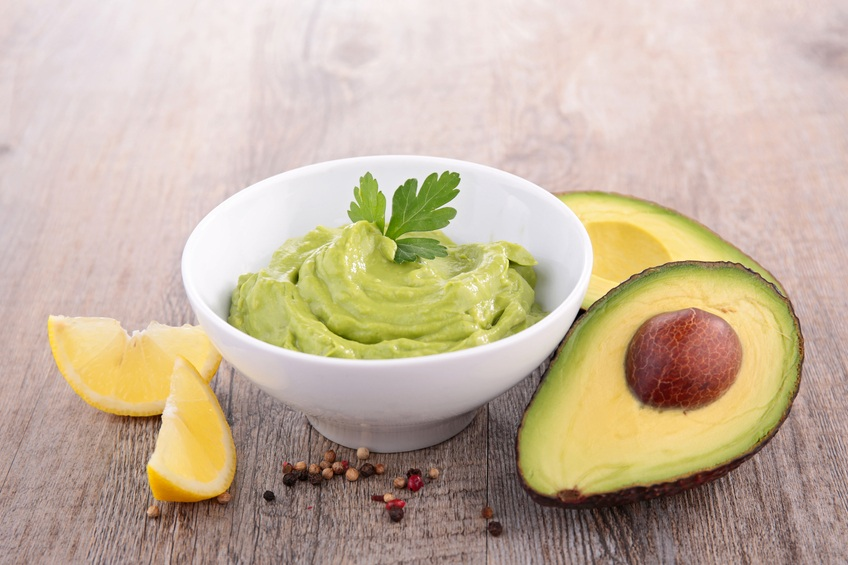 avocado and guacamole on wooden background
