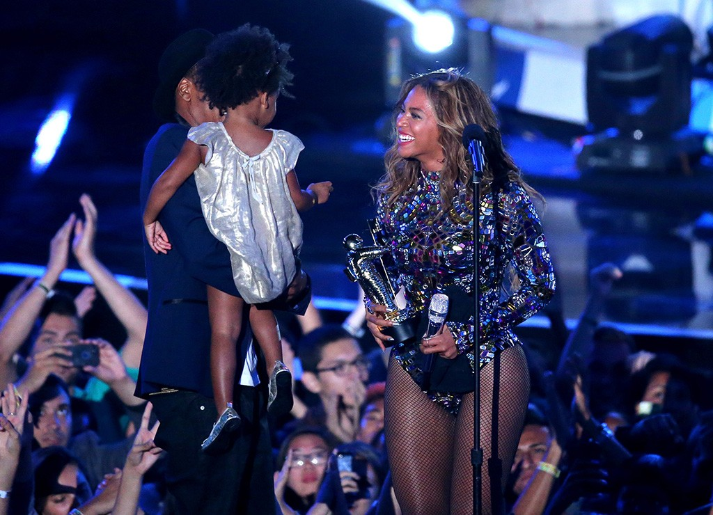 Beyoncé holds up an award and smiles at her daughter and husband while at the 2014 VMAs