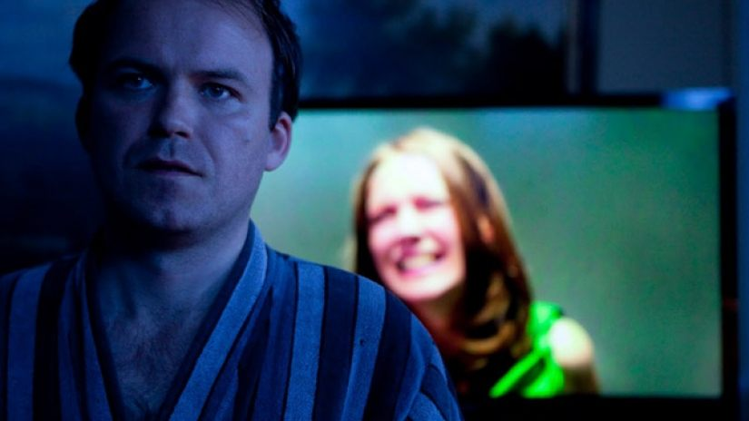 A man in a robe standing in front of a monitor with a crying woman's face on it