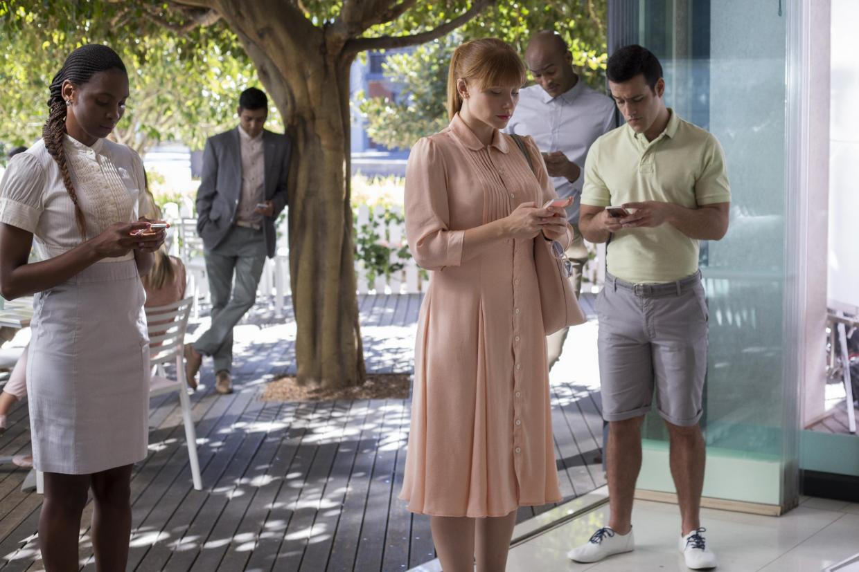 Bryce Dallas Howard and a few others stand near each other, all on their phones