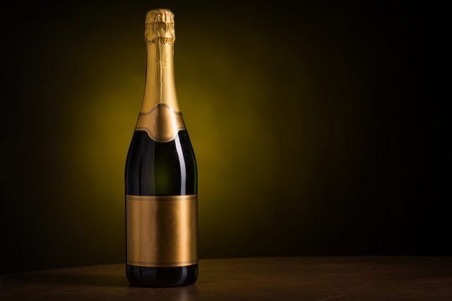 A bottle of champagne with gold foil.