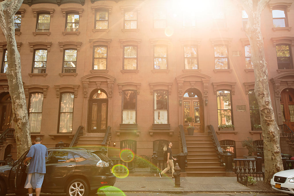 People walk past brownstone townhouses in Brooklyn