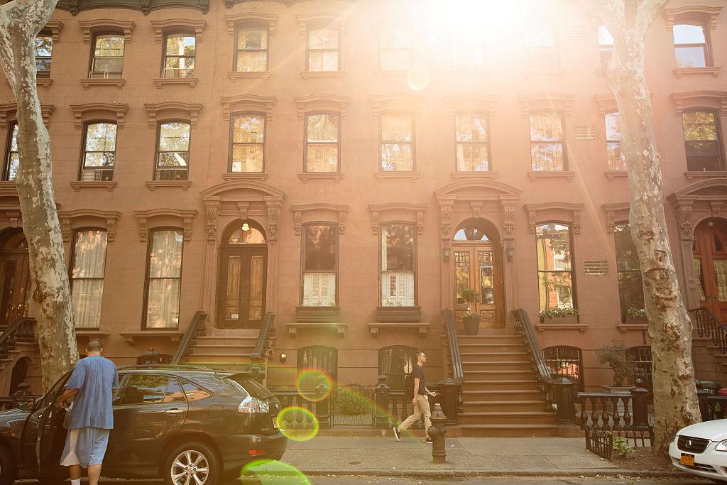 People walk past brownstone townhouses in Brooklyn
