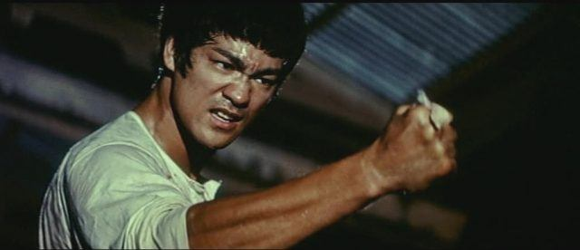 Bruce Lee with his fist extended out, clenched.