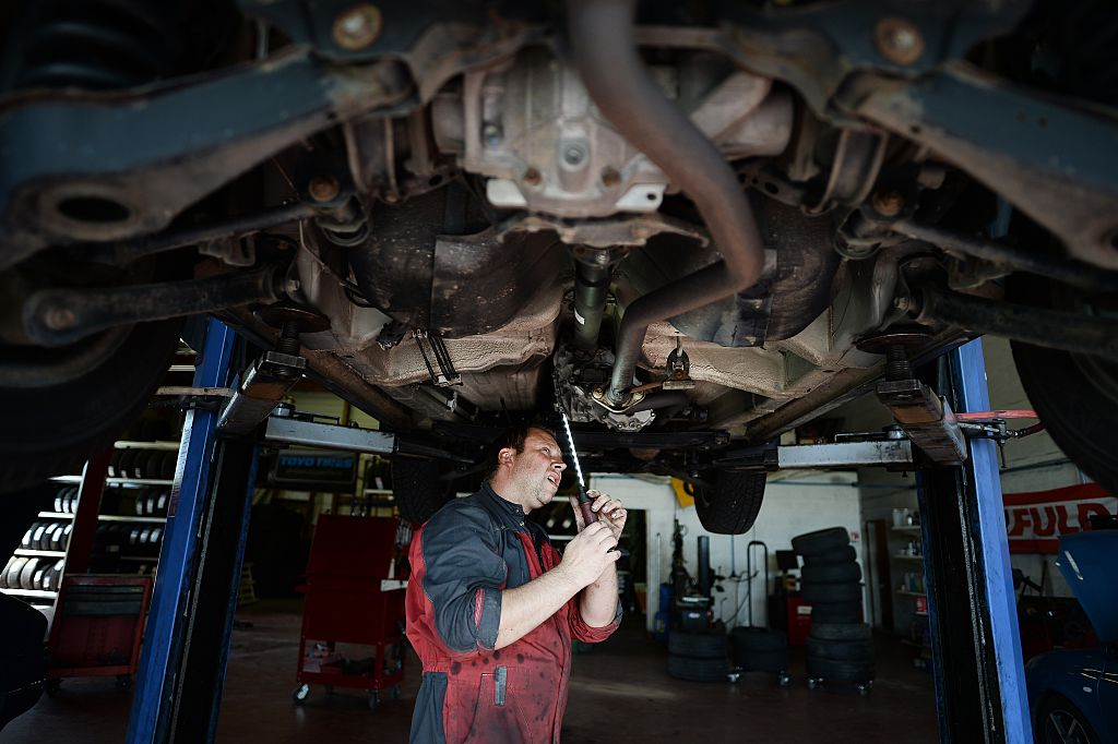 An employee of an automobile garage at work